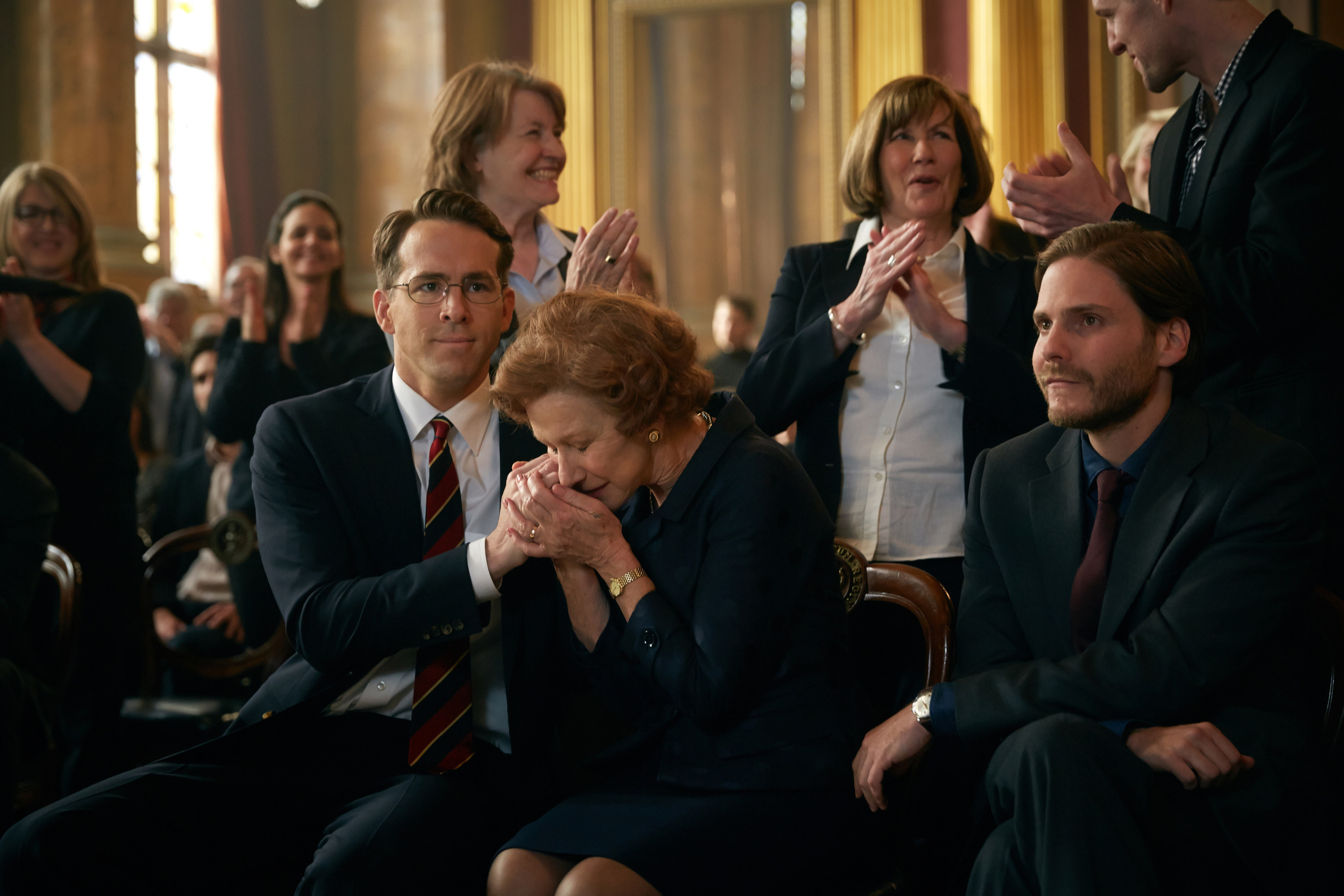 "(L-r) Ryan Reynolds, Helen Mirren, and Daniel Bruhl star in The Weinstein Company's ""Woman in Gold"""